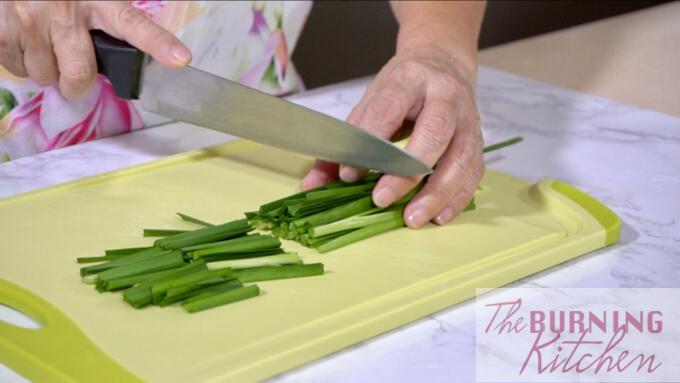 Chopping chives on chopping board