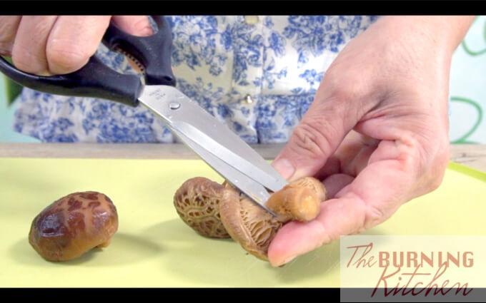 Cutting mushroom stalks off with a pair of scissors