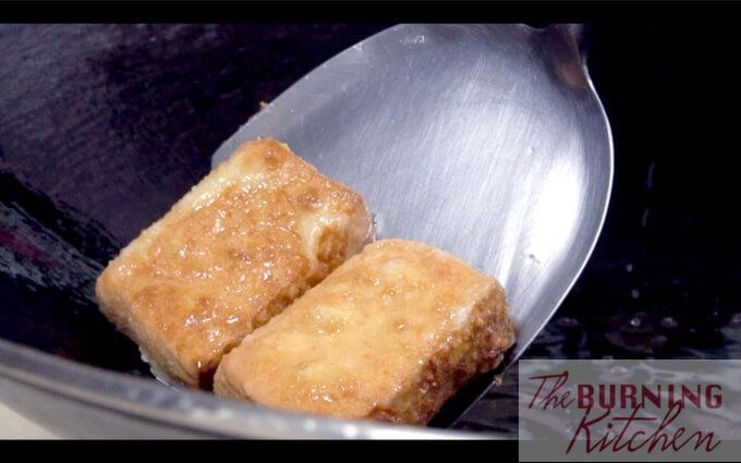 Deep frying Cornflour-coated tofu blocks in oil in wok