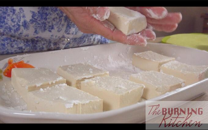 Coating tofu blocks in corn flour in white tray