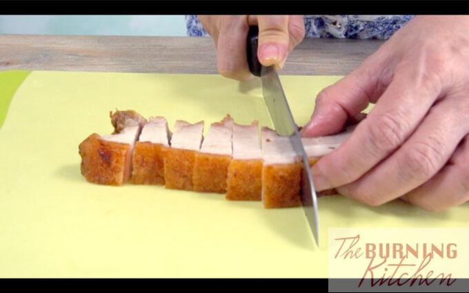 Chopping roast Pork into pieces on a chopping board