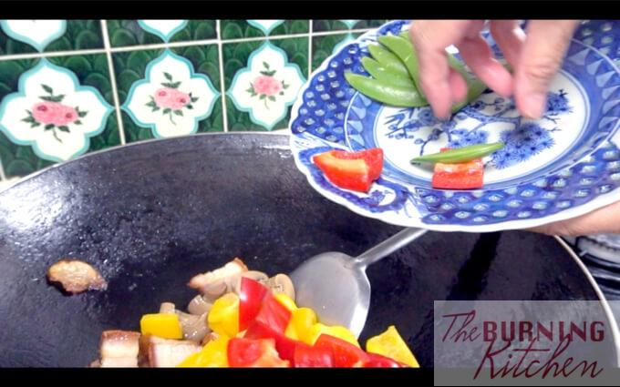 Frying capsicum, mushrooms, sweet peas and roast pork in a wok