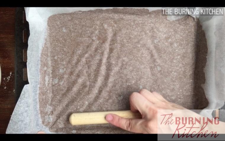 Rolling out gingerbread man cookie dough onto baking tray on baking paper