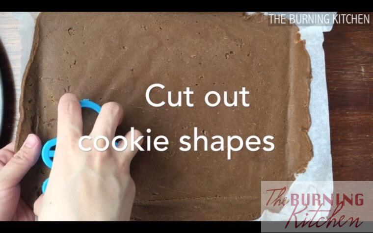 Cutting out gingerbread man shapes with cookie cutter on cookie dough