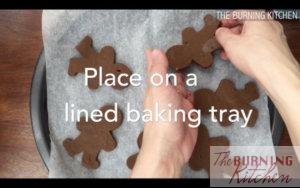 Placing gingerbread man dough pieces on baking paper on baking tray