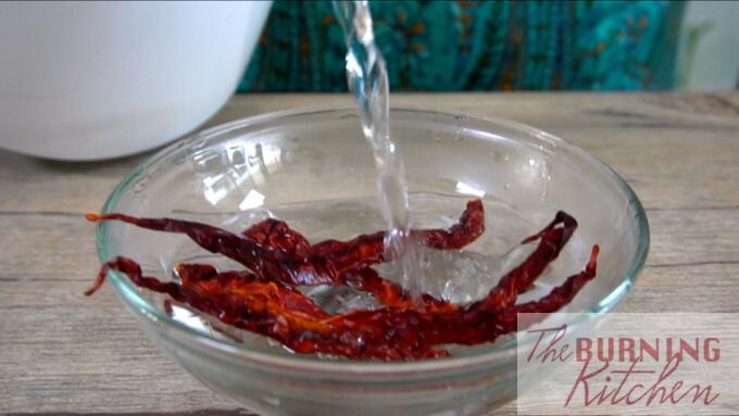 soaking dried chilli in hot water in glass bowl
