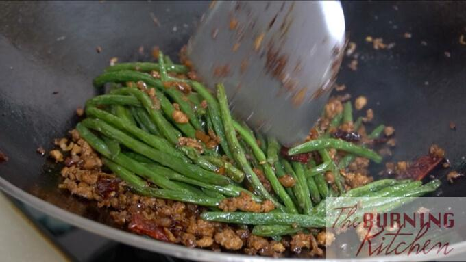 stir frying string beans with minced meat in wok