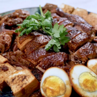 A plate of Chinese braised duck with hard boiled eggs, tofu and chilli sauce