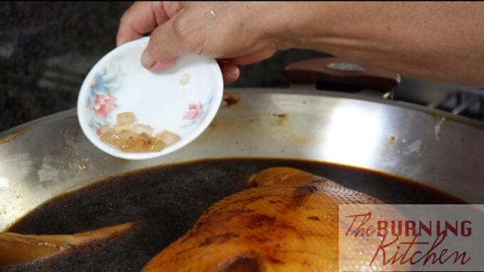 Adding Chinese yellow rock sugar to the pot of duck being braised