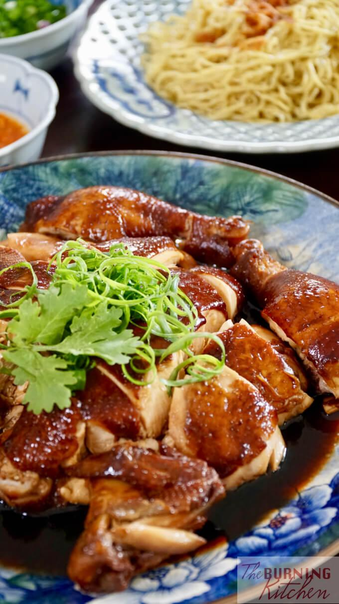Whole chopped soy sauce chicken ready to serve, with chilli sauce, spring onions and noodles