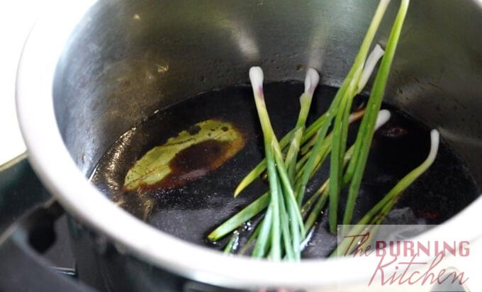 Spring onions being added to the braising sauce for soy sauce chicken