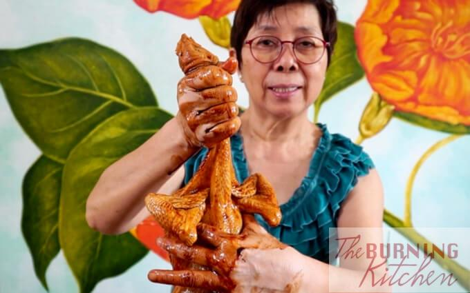 Lady holding up marinate chicken with wings folded backwards
