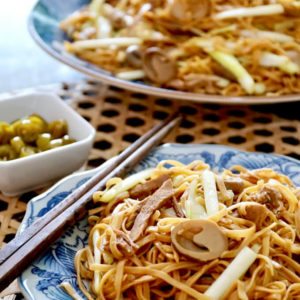 Two plates of Ee Fu noodles with parsley and pickled green chilli