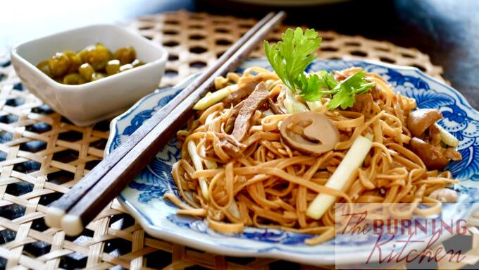 Plate of Ee Fu noodles with parsley and pickled green chilli