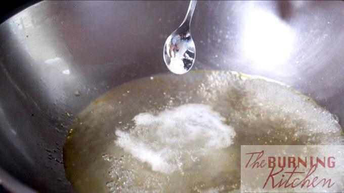 Adding sodium bicarbonate into water in a wok