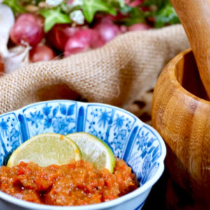 Sambal Terasi in a blue patterned bowl with slices of lime