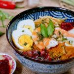 Bowl of Singapore laksa served with sambal chilli