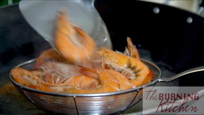 Removing the prawns from the wok after blanching