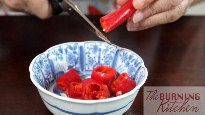 Cutting the large red chilli into pieces