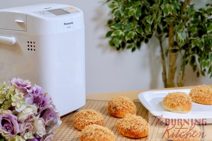 Pork Floss Buns on grill rack and white plate, with Panasonic Bread Maker Machine in the background