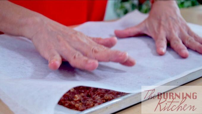 Placing a second baking sheet over the meat mixture