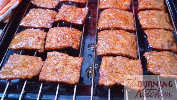 Placing the glazed bak kwa squares on a rack